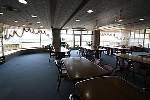 デイルームの写真 大きな窓がある部屋にテーブルが並んでいます