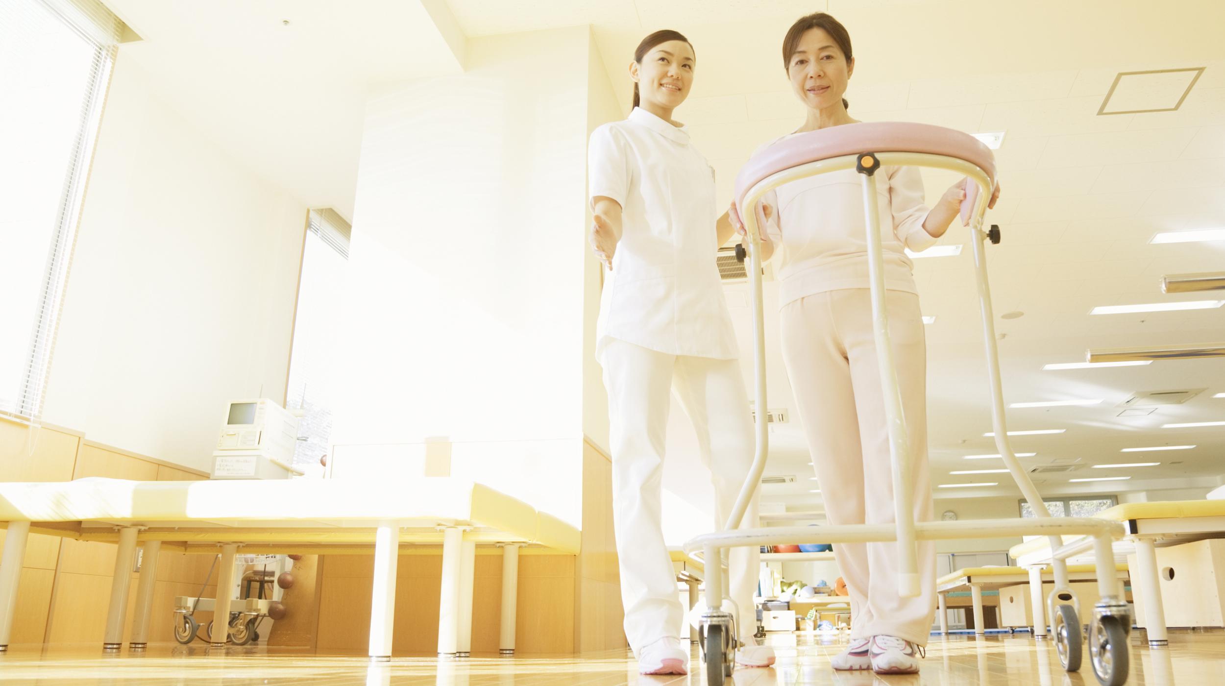 女性の看護師に付き添われて歩行器を使ってリハビリに励む女性の写真